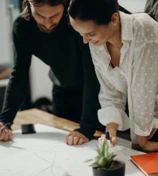 Man And Woman Leaning On Table Staring At White Board On Top 3205570